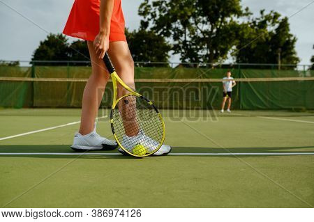 Tennis players with rackets on outdoor court