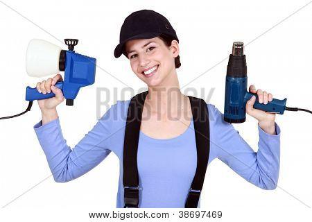 Woman holding paint sprayer and heat gun