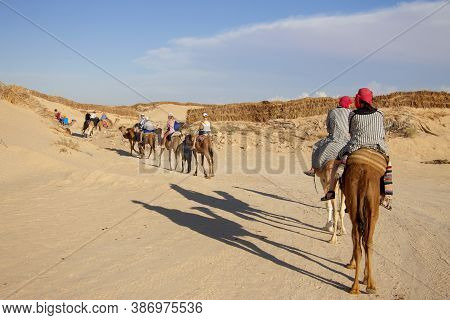 Group Of Tourists Over Dromedary Camel Walking In The Sands Of Sahara Desert, Tunisia, North Africa