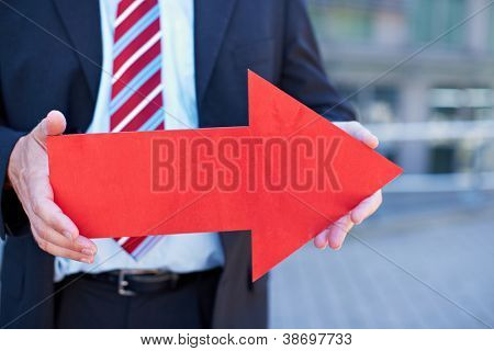 Business man with red arrow pointing to the right