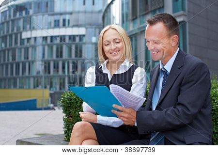 Manager and assistant talking about contract outside the office
