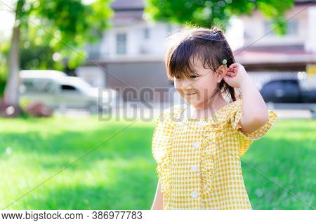 A Bright Little Child Girl Is Walking In A Green Lawn Near The House. The Children Collected White F
