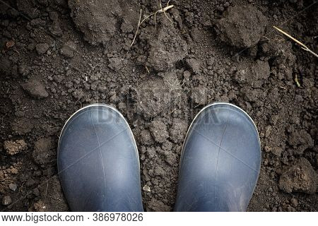 Person In Boots Standing On Soil. Low Key. Close Up.