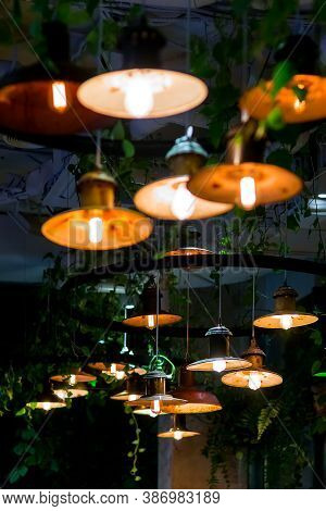 Several Round Loft Style Pendant Lights With Edison Lamps Shine A Warm Light In The Interior Of A Da