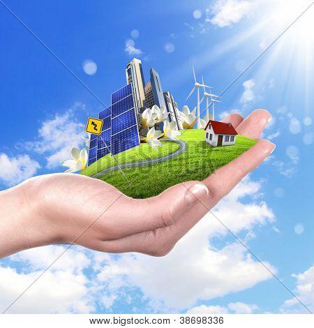 Hands holding a green earth with solar batareis