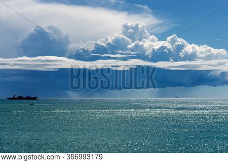 White Clouds In The Blue Sky. Cumulonimbus With Torrential Rain On The Horizon Over The Mediterranea