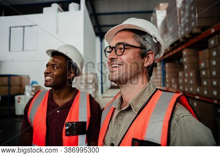 Caucasian Male Worker Wearing Spectacles Laughing With Mixed Race Worker Standing In Factory Warehou