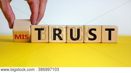 Hand Turns A Cube And Changes The Expression 'mistrust' To 'trust'. Beautiful Yellow Table, White Ba