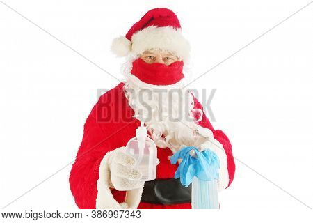 Santa Claus Covid-19. Santa holds a bottle of Hand Sanitizer with a Medical Face Mask and Safety Gloves as a Christmas Gift. Coronavirus is world wide and Dangerous to everyone. Be safe this Christmas