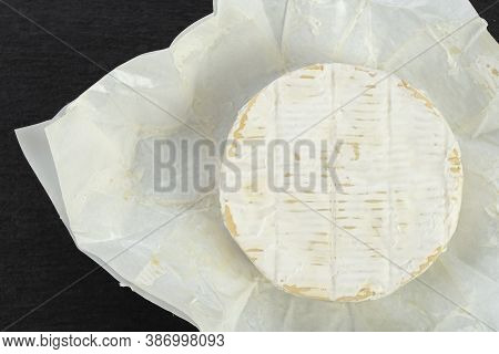 Camembert Cheese Circle On A Black Background. Space For Text. Top View.