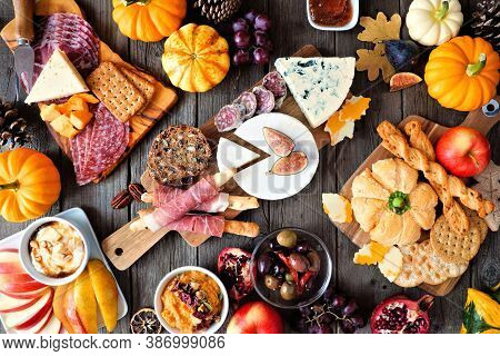 Autumn Theme Charcuterie Table Scene Against A Dark Wood Background. Variety Of Cheese And Meat Appe