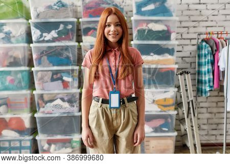 Young Caucasian Woman Smiling At Camera, Posing In Front Of Rack And Boxes Full Of Clothes, Female V