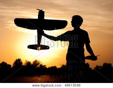 Silhouette of a young man with a model rc airplane against sunset and clouds, with a sunburst