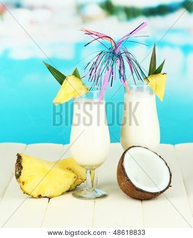 Pina colada drink in cocktail glasses, on bright background poster