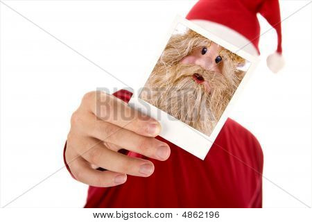 Man In Red Shirt And Santa Hat Holding A Photo In Front Of His Face