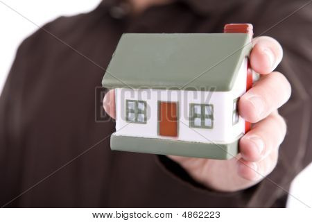 Man Holding A Small House In His Hand