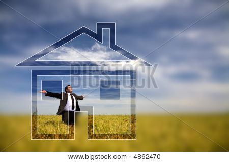 Businessman With His Arms Wide Open In Rural Field With Dream House