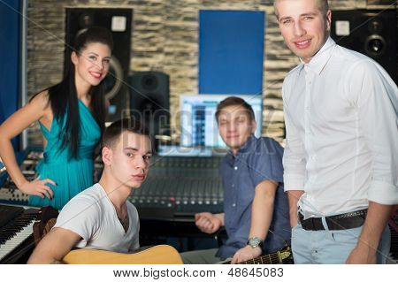 Young musicians in the Recording Studio with equipment, focus on the guy on the right.