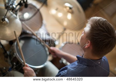 The drummer with headphones plays the drum kit in the studio