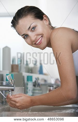 Portrait of happy young woman washing face at bathroom sink