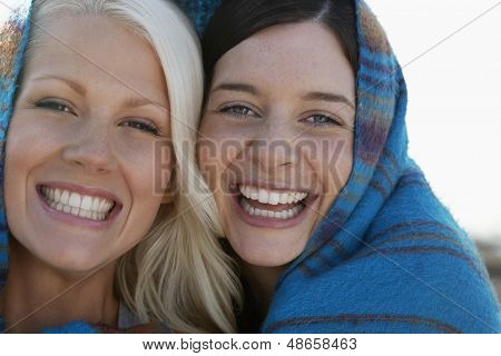 Closeup portrait of joyful young women wrapped in blanket smiling at beach