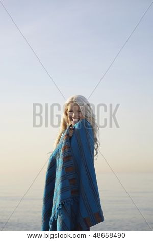 side view portrait of happy young woman wrapped in blanket standing on beach