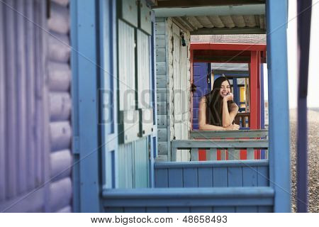 Portrait of beautiful young woman leaning on balustrade of beach house