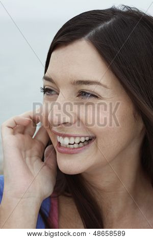 Closeup of cheerful young woman looking away