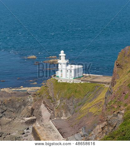 Lighthouse on rock with blue sea