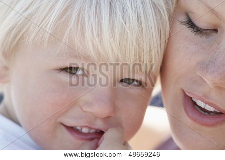Closeup of cute little boy smiling with mother