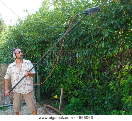 A sound engineer at work during on location recording bird sound in a hedge in Italy using a shotgun microphone with a wind protection shield poster