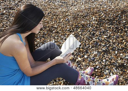 Side view of young woman reading book while sitting on pebbles at beach