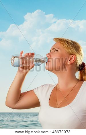 Beautiful Woman Drinking Fresh Water From Bottle On Tropical Beach