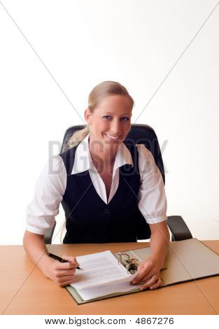 Young Woman Is Working With A Folder At The Desk