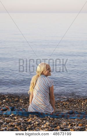 Rear view of young woman looking away while sitting on blanket at beach