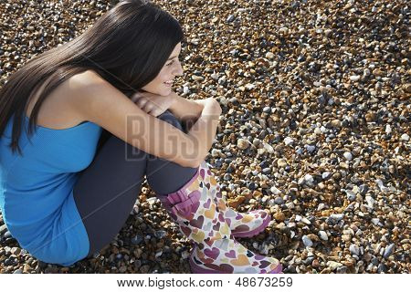 Full length side view of young woman hugging knees while relaxing at beach