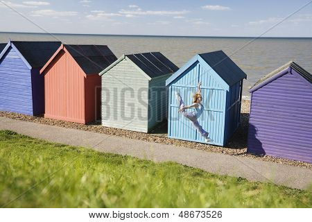 Full length of young woman jumping in front of huts at beach during summer