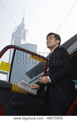 Low angle view of young businessman disembarking from cab