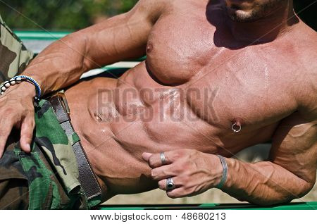 Handsome muscular bodybuilder's torso pecs abs leaning on a side poster