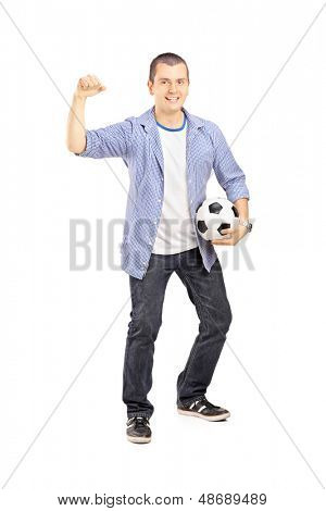 Full length portrait of an euphoric sport fan holding a soccer ball and cheering isolated on white background