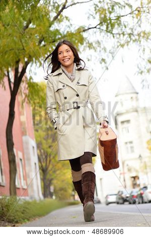Young stylish female professional holding handbag wearing modern trench coat walking in urban city smiling happy. Multiracial Asian Caucasian female model in her 20s.