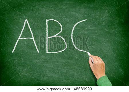 ABC, education and primary school blackboard concept. School teacher writing ABC alphabet in English class or preschool.on chalkboard.