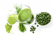 Natural superfood. Alternative medicine. Detox. Ground wheatgrass barley grass blades chlorella pills and spirulina green juice isolated on white background. Healthy living. poster