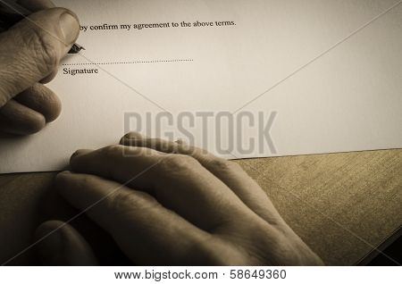 Close up of hands signing document with an austere vintage feel. Ominous lighting gives a sense of threat and a feeling that the signatory is under pressure. Unused hand rests on the table. poster