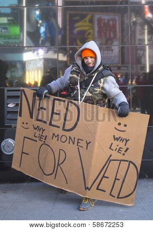 Unidentified man with sign asking for money to buy weed on Broadway during Super Bowl XLVIII week