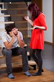 Angry woman standing by bored husband and moaning poster