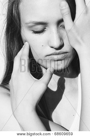 Sensual black and white portrait of a young woman with her eyes closed caressing her face with her crossed hands with a light sensuous seductive touch