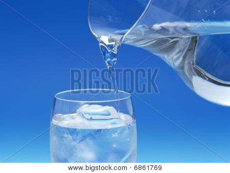 A GLASS OF COLD WATER POURED FROM A JUG