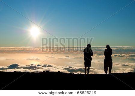 Tourist Silhouette Watching Sunset On The Top Of  Haleakala Volcano On Maui Hawaii