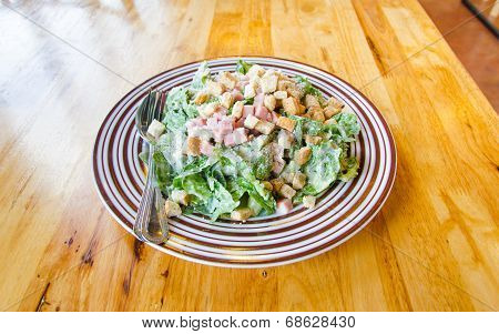 Caesar Salad With Becon And Greens On Wooden Table